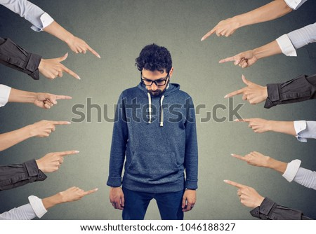 Plenty of crop hands fingers pointing at young man feeling guilty and being introvert.
