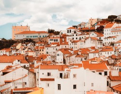 Plenty of traditional crowded antique residential houses with orange clay triangle roofs on the hill of Lisbon, Portugal on a warm sunny day