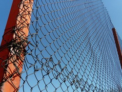 Plexus wire. Metal mesh netting attached to a pole. Part of the fence on the sports ground. In the background is a blue sky. The picture is from below. Fastening a steel fence. Rust and surface damage