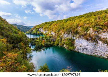 Plitvice cascading lakes with emerald water among the low hills. Autumn trip to Croatia. The concept of ecological and active tourism #1209797893