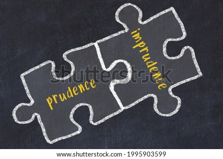 Ploblem solving. Chalk sketch of two puzzles with words prudence and imprudence on black chalkboard Photo stock ©