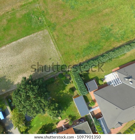 Plots with a meadow, a lawn, a detached house and a terraced house adjoin at one point, plot boundaries look like an abstract cross, Germany