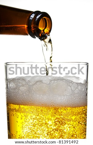 Plouring a golden fresh pilsner beer into a straight sided glass