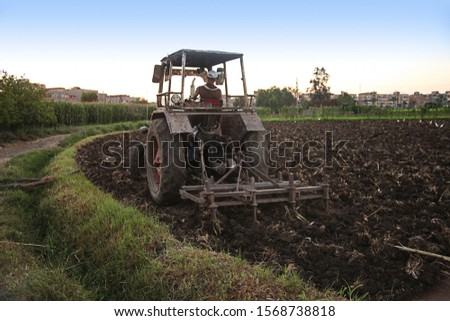 Plow is plowing agricultural land #1568738818