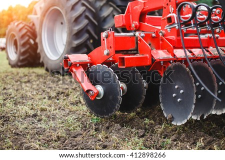 Plow modern tech red tractor close up on an agricultural field. Mechanism. Stockfoto ©