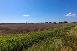 Plowed farm fields. The huge nature reserve Camargue by the sea. Hot summer day in late spring. The Mediterranean coast of France. Concept of eco and photo tourism