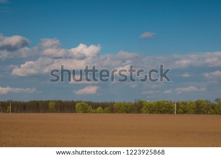 Plowed field withcéoudy sky - outdoor photography #1223925868