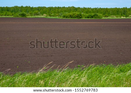 plowed land in arable land for planting crops. spring work in the field plowing #1552769783