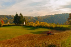 Plowing field. Red tractor. Western Serbian village. Autumn
