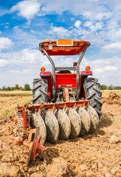 Plowing tracktor in the rice farm .