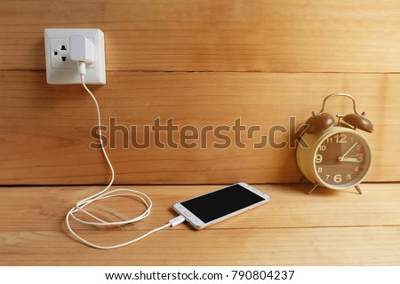 Plug in Adapter power cord charger of mobile phone on wooden floor #790804237