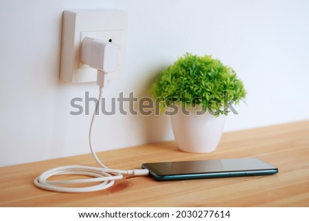 Plug in power outlet Adapter cord charger of smart phone on wooden floor Photo stock ©
