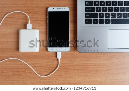 Plug in USB charger from powerbank input mobile phone or cell phone and laptop computer on wooden floor,Top view. #1234916911
