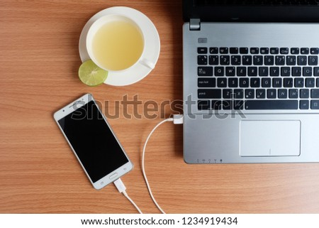 Plug in USB cord charger of the mobile phone with a laptop computer and freshly Lime juice in a white cup, on wooden floor, Top view #1234919434