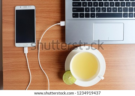 Plug in USB cord charger of the mobile phone with a laptop computer and freshly Lime juice in a white cup, on wooden floor, Top view #1234919437