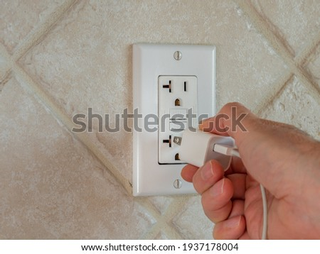 Plugging in electrical usb cord and charger plug in wall outlet. Cell phone power adapter brick and cord in GFCI wall plug.