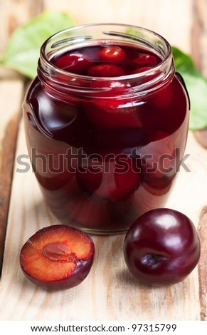 Plum compote glass jar on rough wooden table.