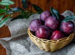 Plum. Fresh plum. Harvest. Autumn harvest. Autumn. Blue plums. Yellow plum. Fresh plums on a wooden surface. Fresh plums on wooden table background.