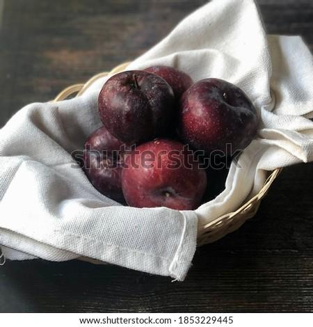 Plum. Fresh plum. Harvest. Autumn harvest. Autumn. Blue plums. Yellow plum. Fresh plums on a wooden surface. Fresh plums on wooden table background. Copy space