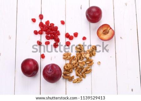 Plum, raisins and walnuts on a white background #1139529413