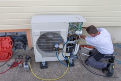 plumber at work installing a circulation heat pump