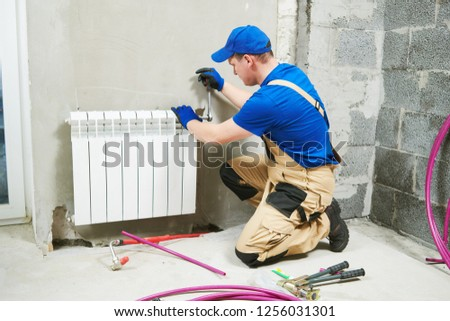 plumber at work. Installing water heating radiator