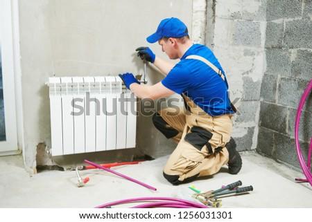 plumber at work. Installing water heating radiator