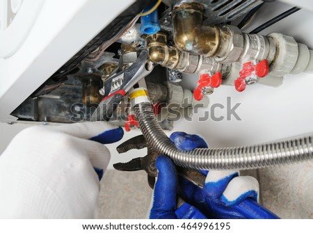 Plumber attaches to pipe gas boiler using adjustable wrench.