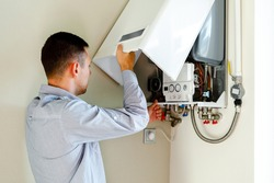 Plumber attaches Trying To Fix the Problem with the Residential Heating Equipment. Repair of a gas boiler