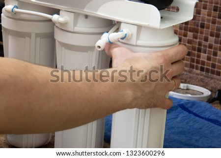 plumber change the water filter. installing osmosis in home. male hand spins the cartridge. #1323600296
