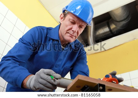 Plumber cutting grey pipe