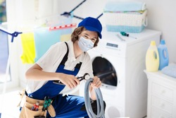 Plumber emergency service during coronavirus outbreak. Technician in face mask repairing broken washer. Maintenance of home and household appliance in lockdown and quarantine. Urgent repair.