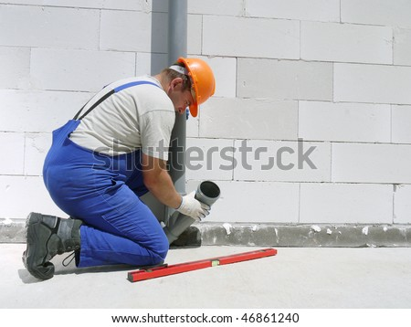 Plumber fitting pvc sewage pipes inside newly built house