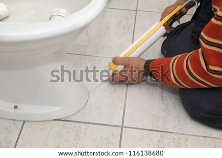 Plumber fixing bidet in a washroom with  silicone cartridge