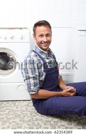 Plumber fixing broken washing machine - stock photo
