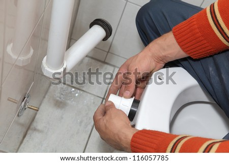Plumber fixing plastic tube of wall mounted toilet cistern
