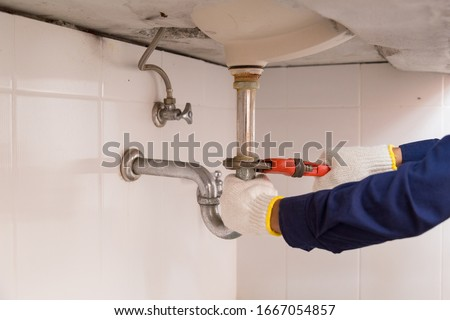 Plumber fixing white sink pipe with adjustable wrench. Foto stock ©