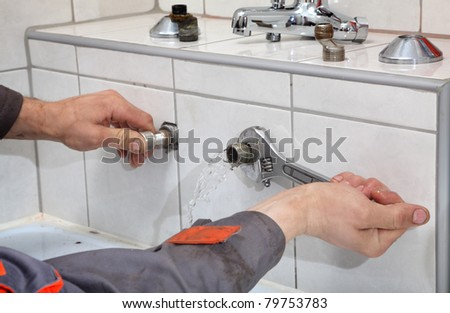 Plumber hands fixing water pipe with spanner and with leaking water from pipe
