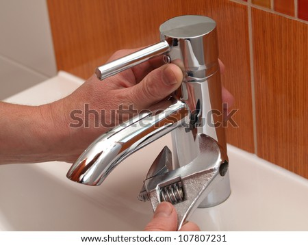 Plumber hands repair water tap with spanner - stock photo