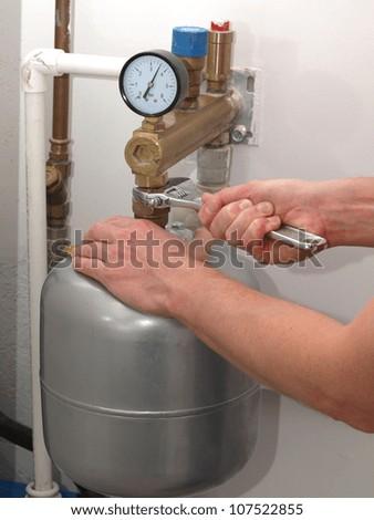 Plumber hands repairing pressure vessel with spanner