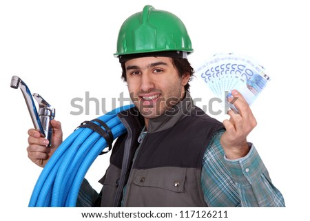 Plumber holding a tap and his hard-earned salary
