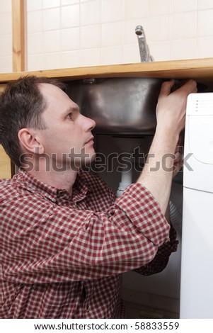 Plumber installing a kitchen sink