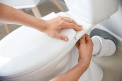 Plumber installing toilet in restroom