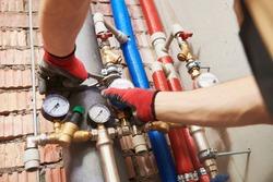 plumber installing water equipment - meter, filter and pressure reducer