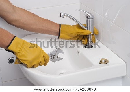 plumber installs a new faucet for a sink #754283890