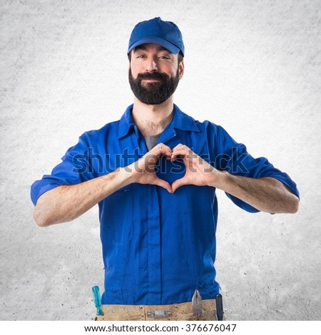 Plumber making a heart with his hands over textured background #376676047