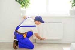 Plumber man is blocking repairs radiators of heating battery in apartment tap