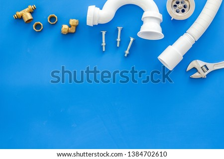 Plumber profession with gear and instruments for repair tubes on blue background top view copyspace #1384702610