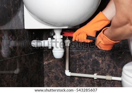 Plumber repairing sink pipe in bathroom #543285607