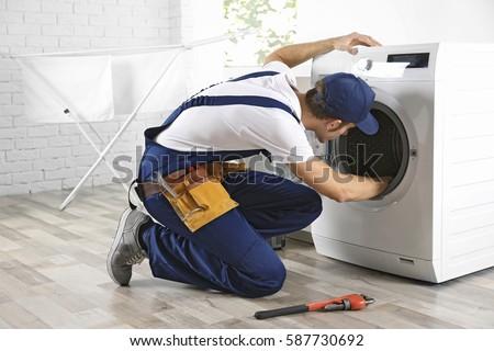 Plumber repairing washing machine #587730692